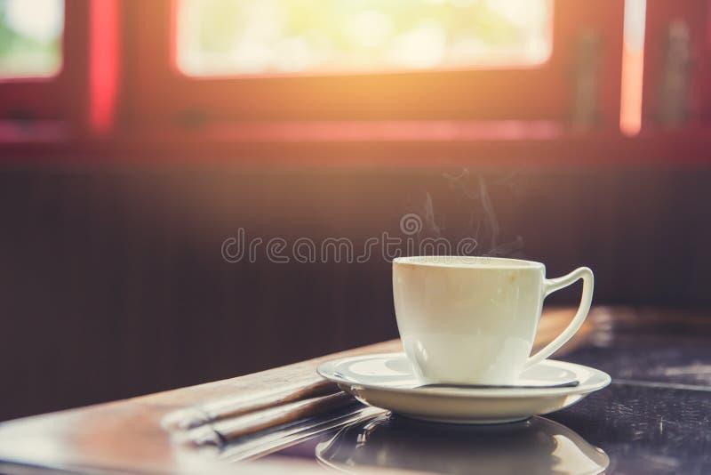 escoja la taza blanca de café caliente del café express con la luz del sol de la mañana de ventanas imagenes de archivo