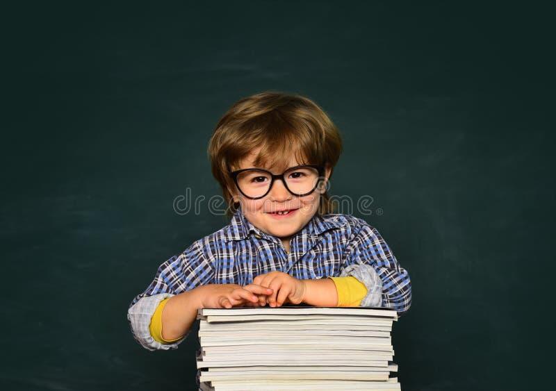 Escola das crian?as Menino pr?-escolar pequeno bonito da crian?a em uma sala de aula Estudante Educa??o home Fundo do quadro-negr fotos de stock