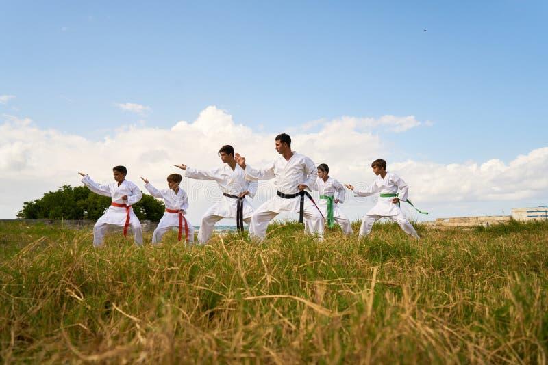 Escola do karaté com aquecer-se dos instrutores e dos meninos imagens de stock royalty free