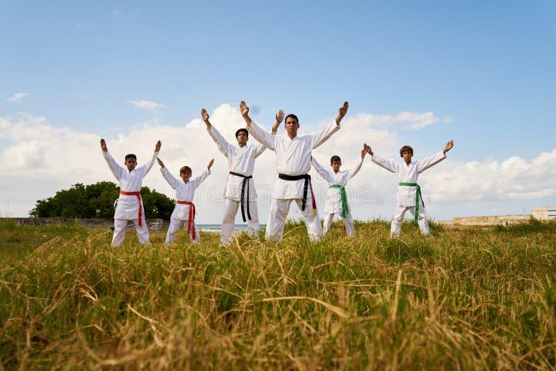 Escola do karaté com instrutores e Young Boys que mostra a tecnologia de combate fotos de stock