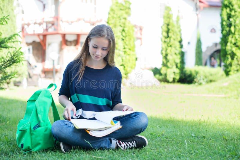 Escola ou universitária que sentam-se com livro e saco que estuda em um parque imagens de stock