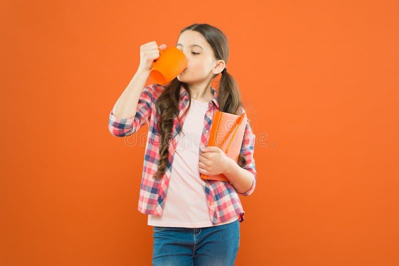 A escola pode esperar Chá bebendo da criança com leite para a menina bonito do café da manhã com copo de chá e livro de nota na l imagens de stock royalty free