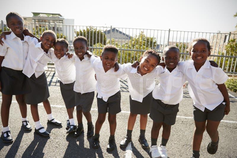 A escola primária caçoa em África que levanta no campo de jogos da escola imagens de stock