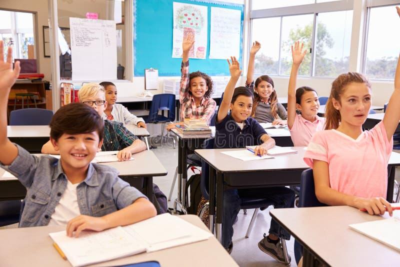 A escola primária caçoa em uma sala de aula que levanta suas mãos imagem de stock royalty free