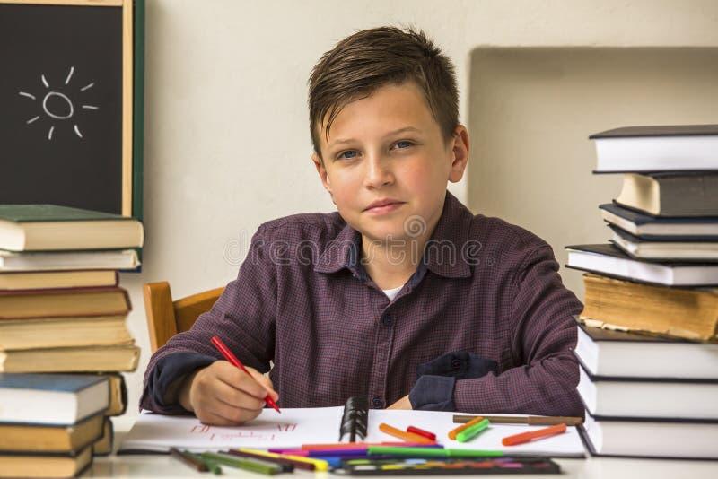 A escola primária do aluno faz trabalhos de casa aprendizagem foto de stock