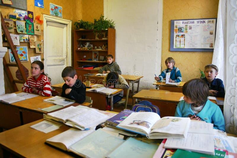 A escola rural no campo, estudantes senta-se em suas mesas nos clas imagens de stock
