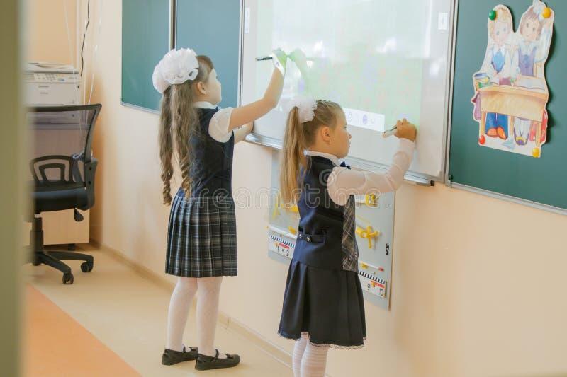 escola Sala de aula Duas meninas com fitas brancas e vestidas na roupa da escola, escrevem no whiteboard interativo imagens de stock