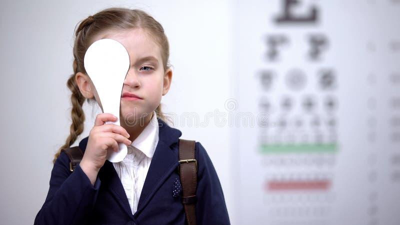 Escolar cerrando un ojo para un examen de visión completo, diagnóstico de vista foto de archivo