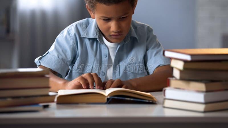 Escolar concentrado que hace la preparación que se sienta en el escritorio, el estudiar intensivo fotos de archivo