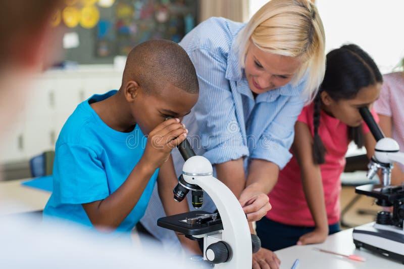 Escolar de los niños que mira a través del microscopio imagen de archivo