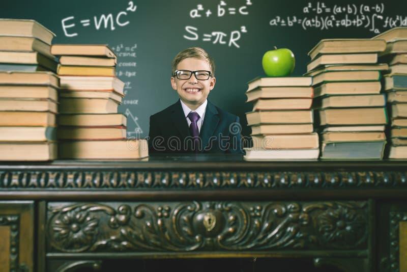 Escolar elegante que se sienta en la tabla con muchos libros fotos de archivo libres de regalías