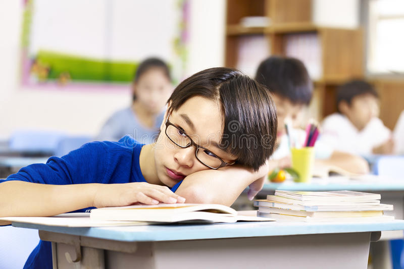 Escolar elemental asiático que piensa en sala de clase imagenes de archivo