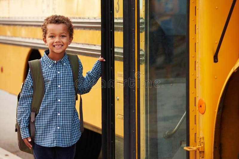 Escolar elemental que consigue sobre un autobús escolar amarillo imagenes de archivo
