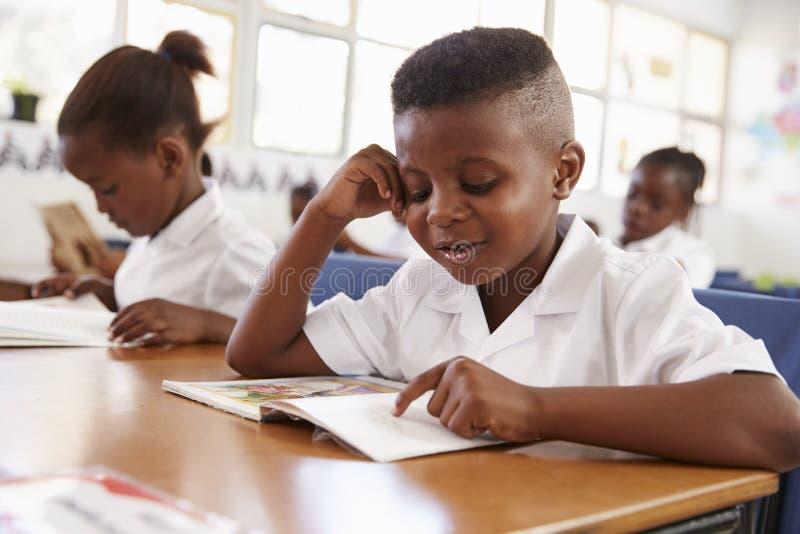 Escolar elemental que lee un libro en su escritorio en clase imagen de archivo