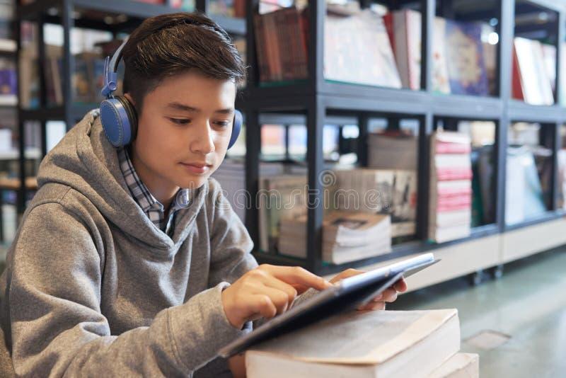 Escolar en auriculares en biblioteca con la tableta fotos de archivo libres de regalías
