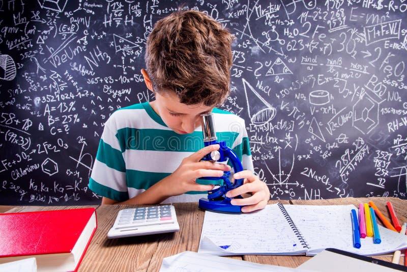 Escolar en el escritorio con el microscopio, pizarra grande fotos de archivo
