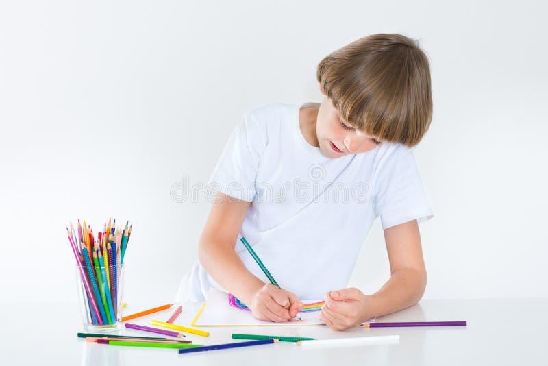 Escolar feliz paiting en un escritorio blanco fotografía de archivo libre de regalías
