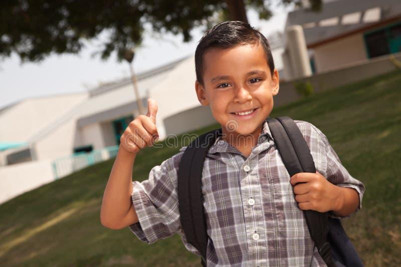 Escolar hispánico joven feliz con los pulgares para arriba fotografía de archivo