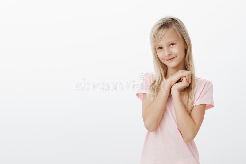 Escolar primario que hace mirada del ángel para conseguir qué quiere La niña adorable con el pelo justo, sosteniéndose da junta c foto de archivo