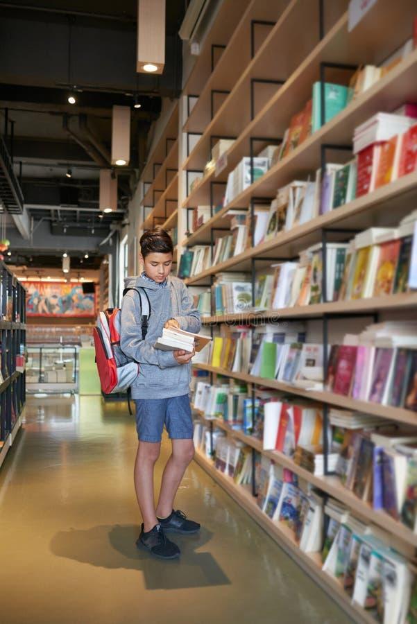 Escolar que se coloca en biblioteca con los libros y la mochila imágenes de archivo libres de regalías
