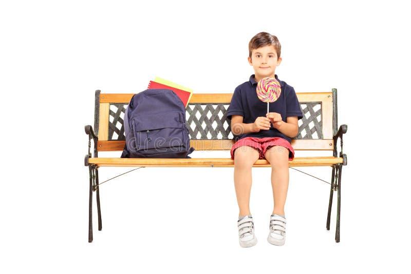 Escolar que se sienta en un banco y que sostiene una piruleta del caramelo imágenes de archivo libres de regalías