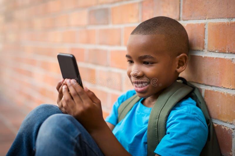 Escolar que usa el teléfono elegante fotografía de archivo libre de regalías