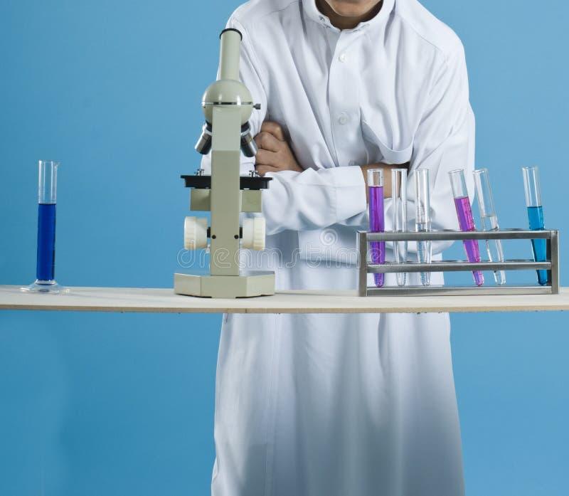 Escolar que usa un microscopio con las sustancias químicas en tubos de ensayo imagenes de archivo