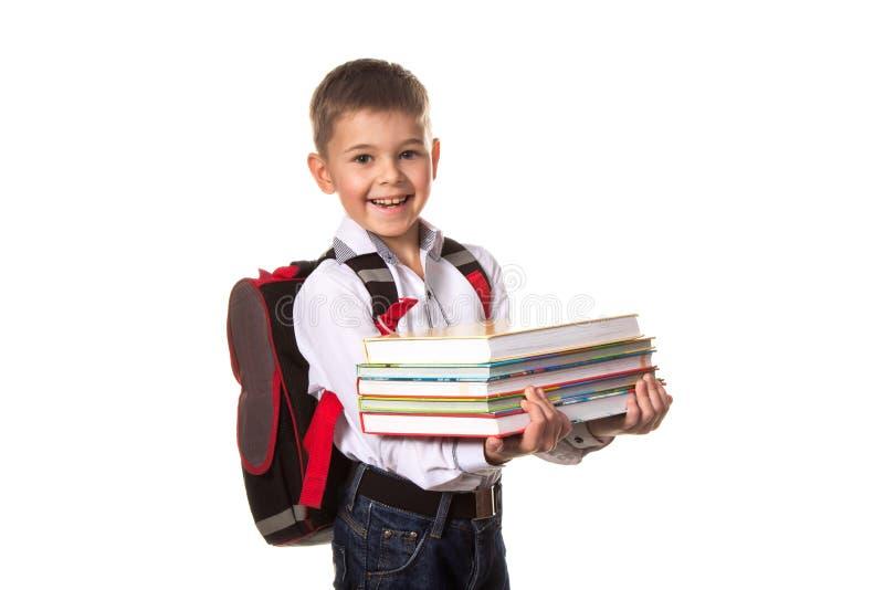 Escolar sonriente con la mochila que sostiene los cuadernos, en el fondo blanco imagen de archivo libre de regalías