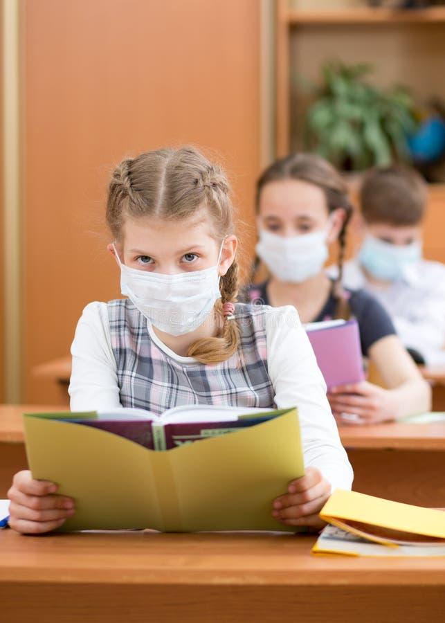 Escolares con máscara de protección contra el virus de la gripe en clase fotos de archivo
