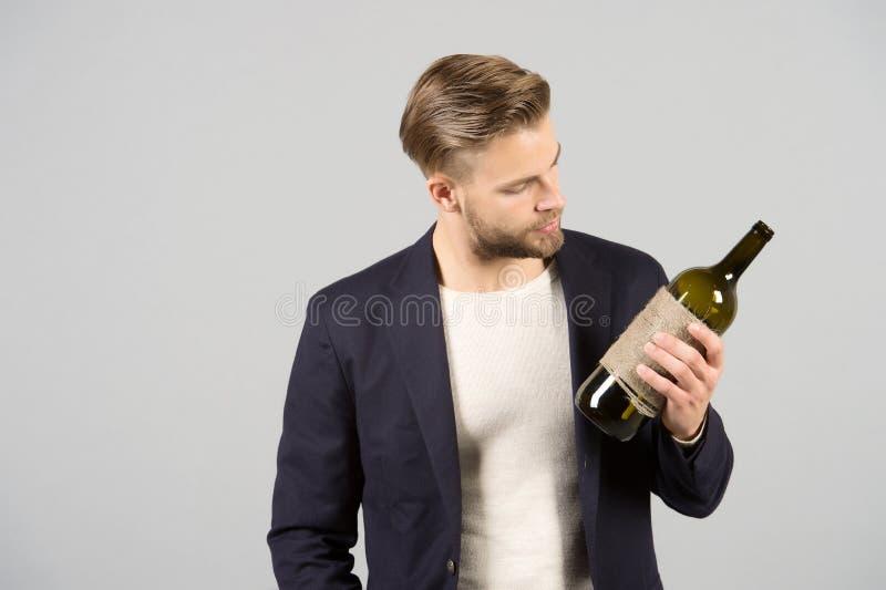 Escolha agradável O homem guarda a bebida do álcool da garrafa Aspectos sociais e culturais de beber Garrafa de cálculo pensativa fotos de stock