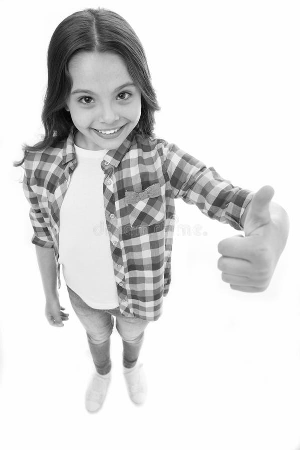 Escolha agradável Recomende altamente A menina da criança mostra o polegar acima do gesto, fundo branco isolado Criança de sorris fotografia de stock