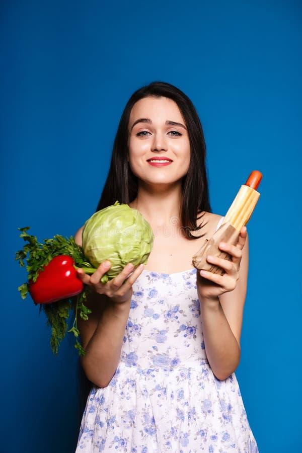 Escolha difícil do alimento, uma morena bonita com vegetais e hotdog imagens de stock