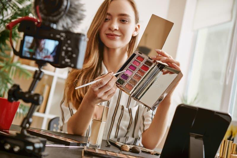 Escolha-o Blogger fêmea bonito que apresenta uma paleta da composição e que sorri ao olhar a câmera fotos de stock