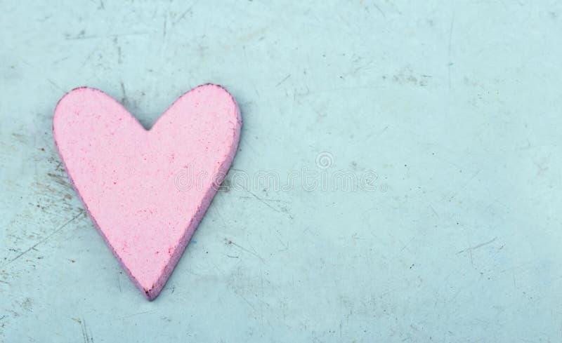 Escolha o coração cor-de-rosa na luz - fundo de madeira azul imagens de stock royalty free