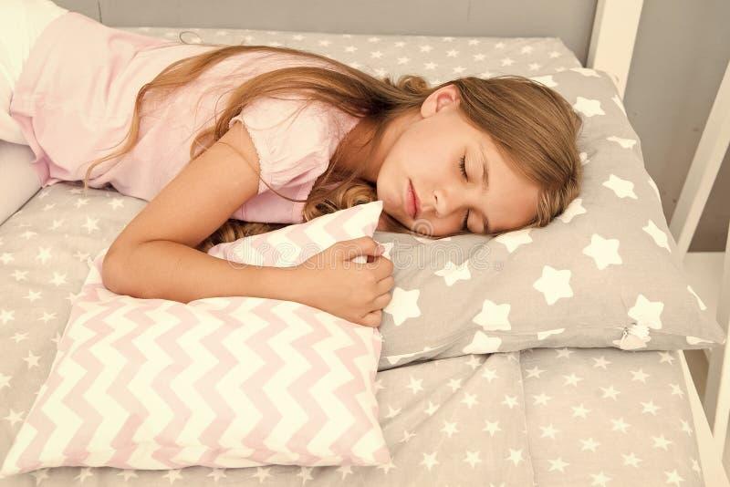 Escolha o descanso apropriado relaxar bem Pontas saud?veis do sono A menina dorme em pouco fundo do roupa de cama do descanso Cri fotos de stock royalty free
