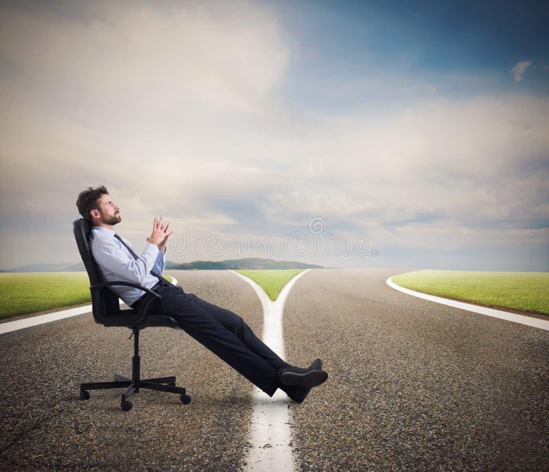 Escolhas difíceis de um homem de negócios no estradas transversaas Conceito da confusão imagem de stock