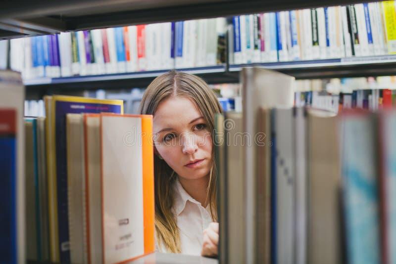 Escolhendo o livro na biblioteca fotos de stock royalty free