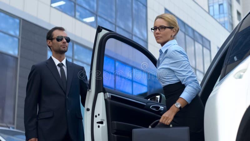 Escolta en puerta de coche de la abertura del traje al jefe femenino, servicio de lujo, éxito foto de archivo libre de regalías