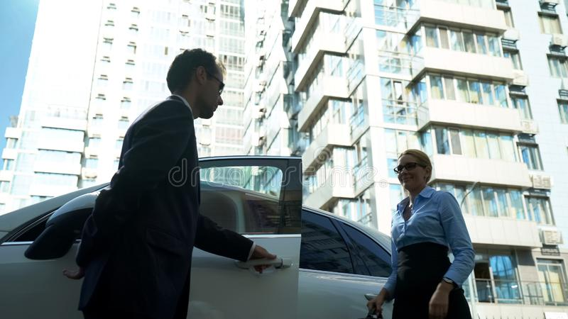 A escolta pessoal abre portas de carro à senhora, segurança para o político, celebridade imagens de stock royalty free