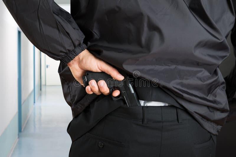 Escolta Removing Handgun imagen de archivo libre de regalías