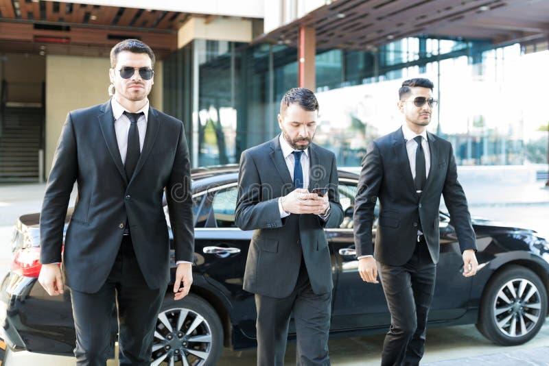 Escoltas jovenes que caminan por el hombre de negocios imagenes de archivo