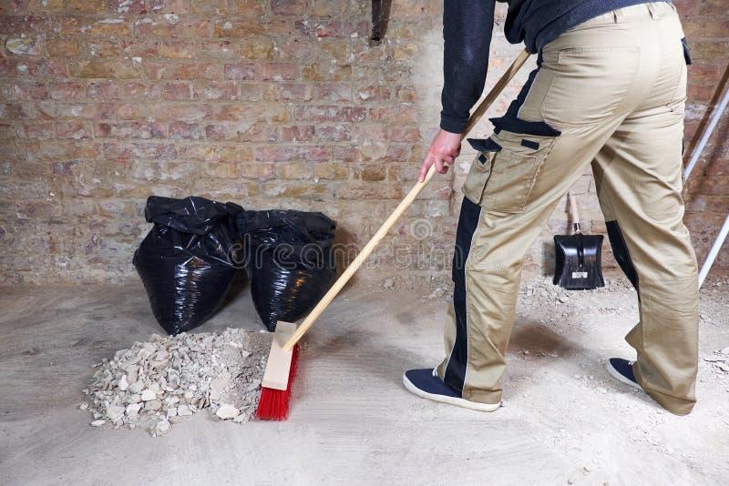 Escombros y polvo arrebatadores del trabajador con la escoba roja imágenes de archivo libres de regalías