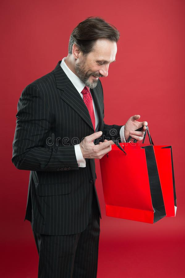 Escompte choquant Homme d'affaires mûr tenant un sac en papier cadeau fond rouge Concept commercial Don de Noël Heureux photographie stock