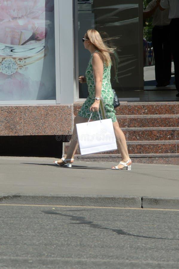 escomptes Vente Jeune femme aux longues jambes dans une robe verte et des talons hauts blancs descendant la rue après les boutiqu photos stock