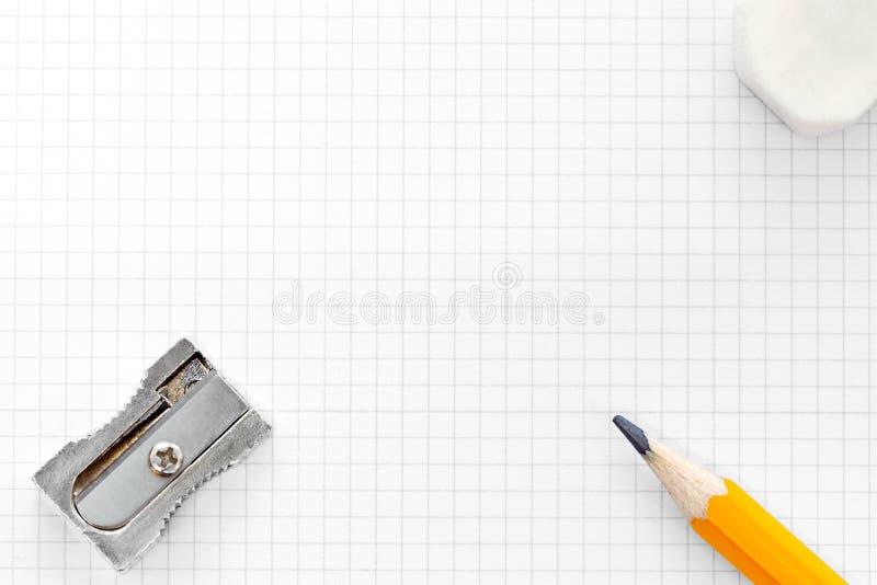 Esconda el borrador y los sacapuntas ajustados del papel de gráfico foto de archivo