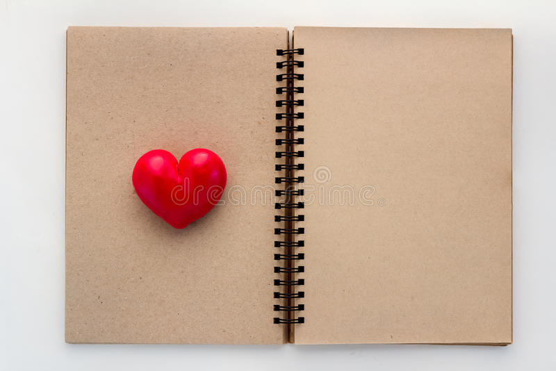 Esconda el cuaderno abierto con el corazón rojo imagen de archivo