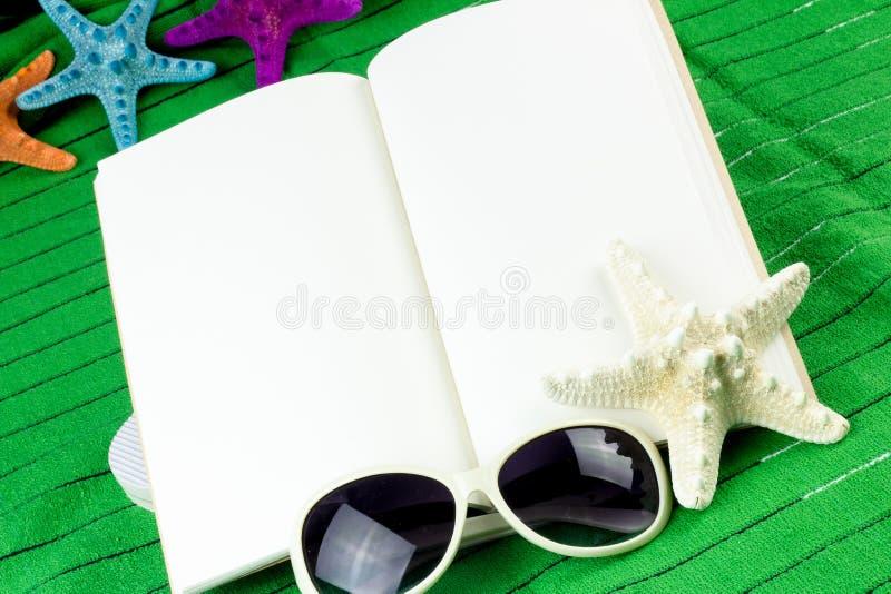 Esconda el libro abierto en una toalla de playa imagen de archivo