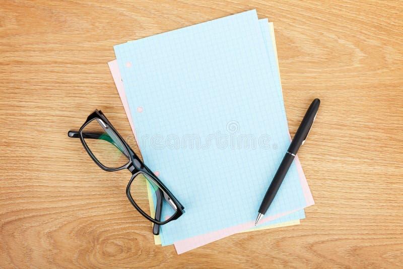 Esconda el papel alineado con los materiales de oficina y los vidrios foto de archivo