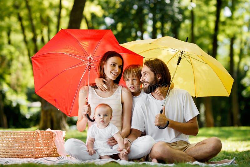 Escondendo do sol sob guarda-chuvas vermelhos e amarelos grandes mãe, o pai e suas crianças estão sentando-se na cobertura e imagens de stock royalty free