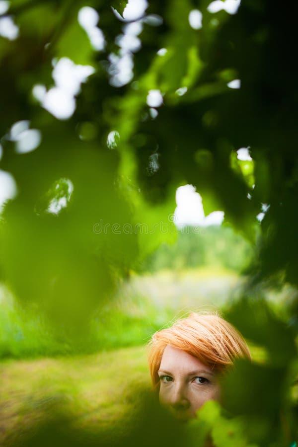 Esconder louro avermelhado da mulher fotografia de stock